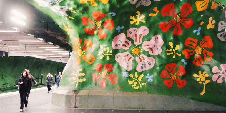 Alby subway station in Stockholm. Large colorful flowers are painted on the station's green cave walls.