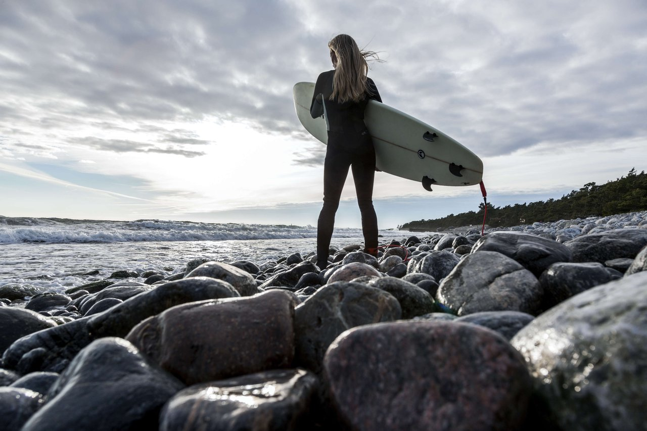 A woman holds a surf board on a stony beach on Torö, an island in the Stockholm archipelago.