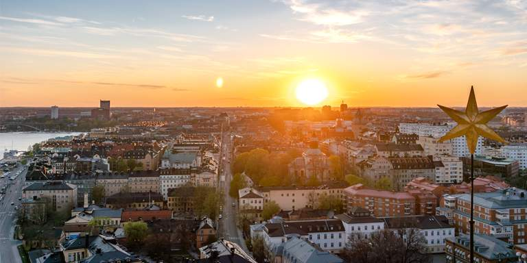 The sun is going down over Kungsholmen in Stockholm, view from the City Hall Tower in April.