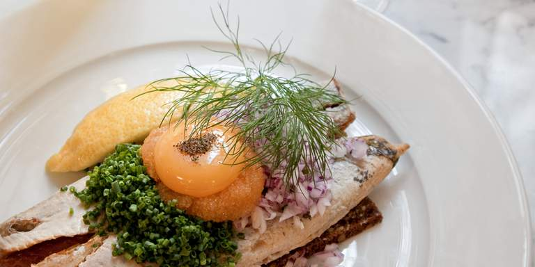 Classic Swedish food. Fried herring on rye bread, topped with chives, an egg yolk, red onion, dill and roe. There are several good restaurants in Stockholm where you'll be treated to classic Swedish cuisine.