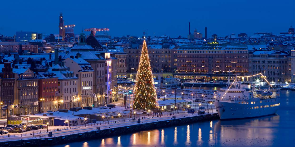 Winter evening in Stockholm. Pictured is the traditional Christmas tree that is raised every year at Skeppsbron in Old Town, which is visible behind it.