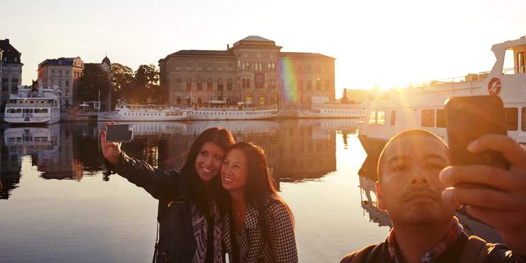 A summer evening in Stockholm. Two young women are taking a selfie by the water, with Nationalmuseum visible in the distance.