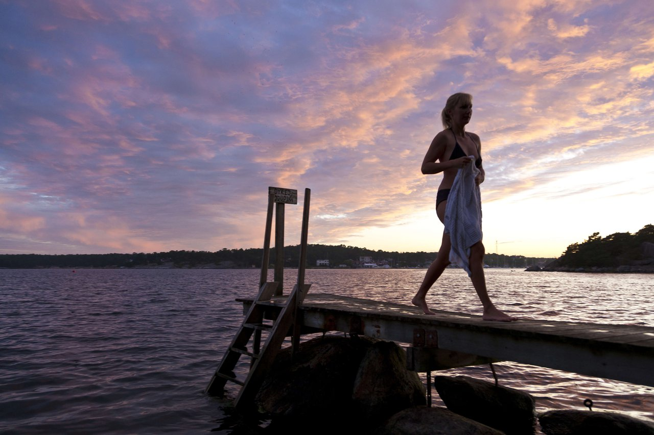 A woman walks on a jetty after going for a swim on the island of Möja in the Stockholm archipelago.