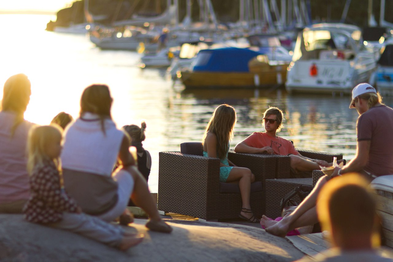A group of people sit outdoors in the summer at sundown on the island of Grinda in Stockholm's archipelago.
