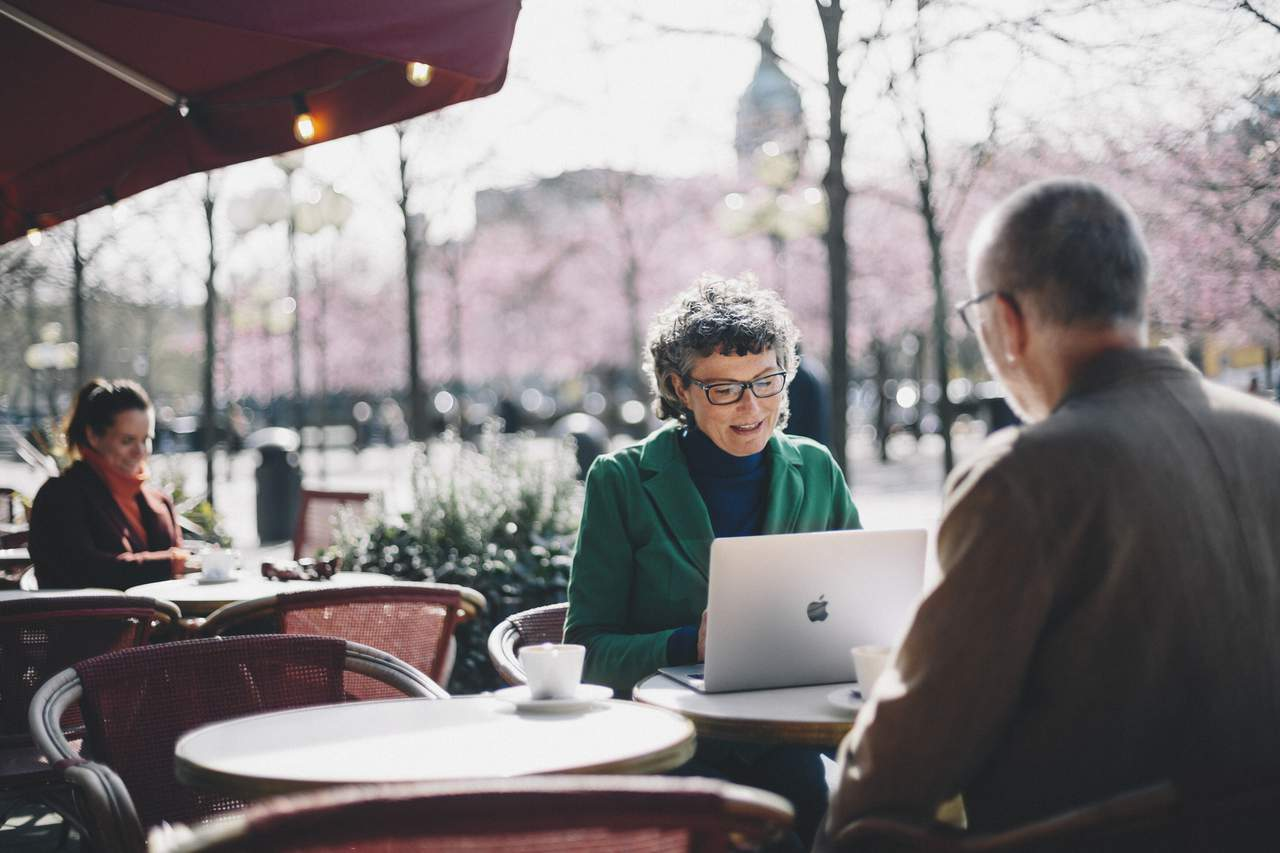 Two people sit working outdoors at a café in Kungsträdgården in Stockholm with cherry blossoms in the background.