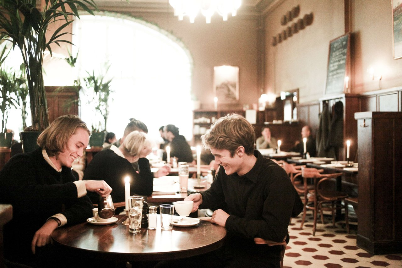 Friends drink coffee at Pelikan, a restaurant and beer hall in Södermalm, Stockholm.