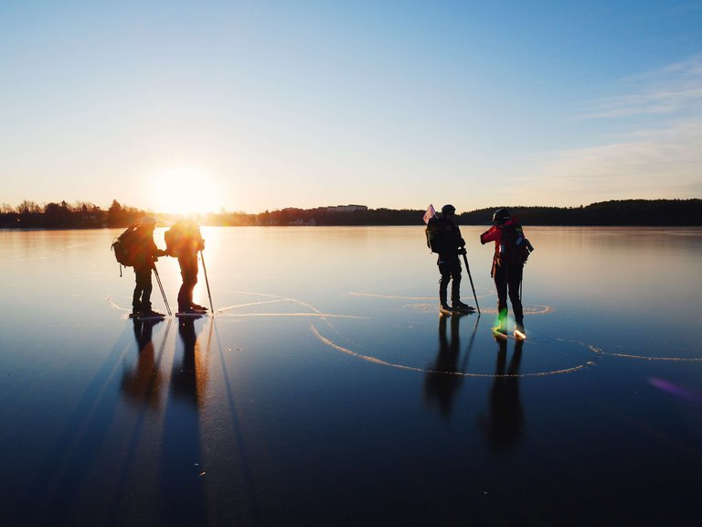 4 people ice skating on a frozen late on a sunny winter day