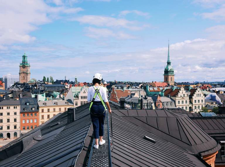 A person in a safety harness takes a rooftop tour on the island of Riddarholmen in Stockholm.