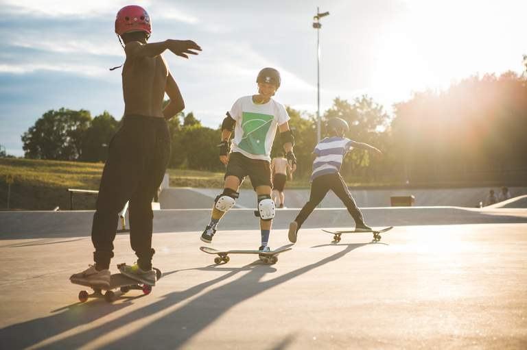 Teenagers skating in the sunlight on a summer day