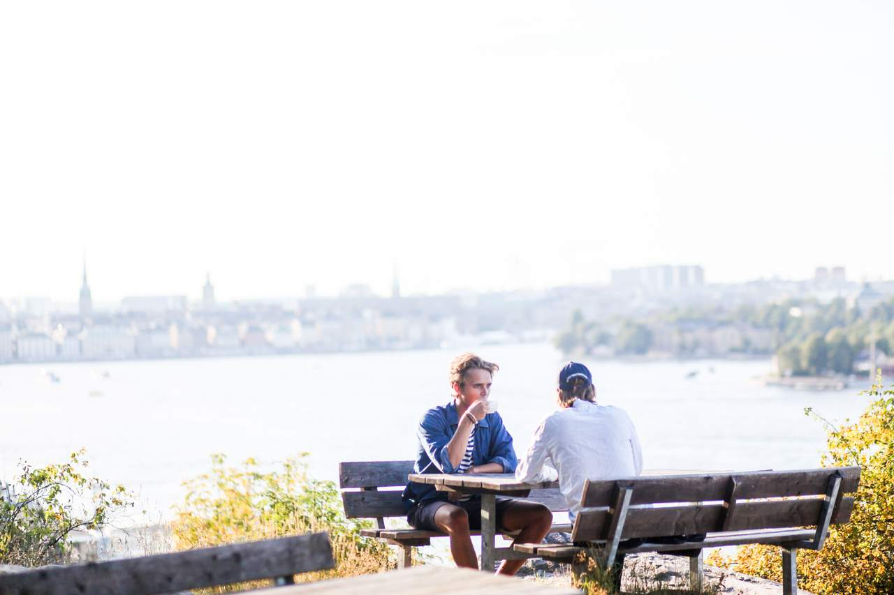 Two men enjoy a coffee break outdoors at a picnic table on Södermalm in Stockholm.
