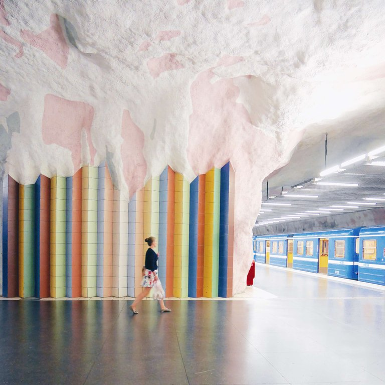 A woman walks towards a subway train against a backdrop of a tiled wall in pastel shades at Mörby Centrum in Stockholm.