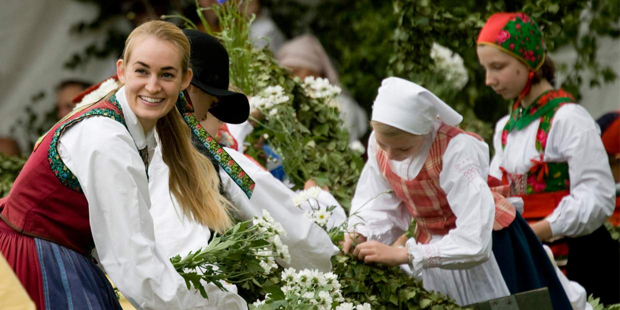 Teenagers dressed in colorful old traditional Swedish costumes, during Midsummer celebrations at the Skansen open-air museum in Stockholm. Midsummer is celebrated at the longest day of the year—when the sky never darkens. It's one of the most characteristic and beloved Swedish traditions.