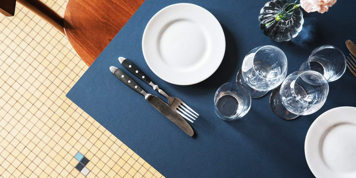 A table set for one, glasses and cutlery against an indigo blue table. A pale pink rose in a vase decorates the table at Bar Agrikultur.